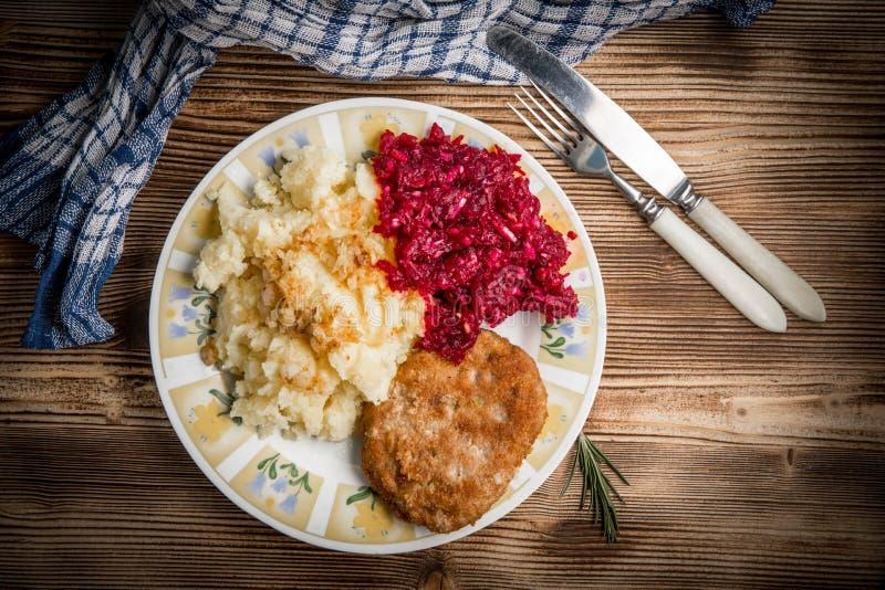 Schweinefleischkotelett mit Hackfleisch diente mit gekochten Kartoffeln und Biene stockfotos