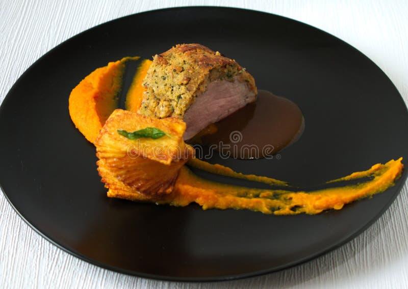 Schweinefleischleiste mit Kürbiscreme und Stapelkartoffel lizenzfreie stockbilder