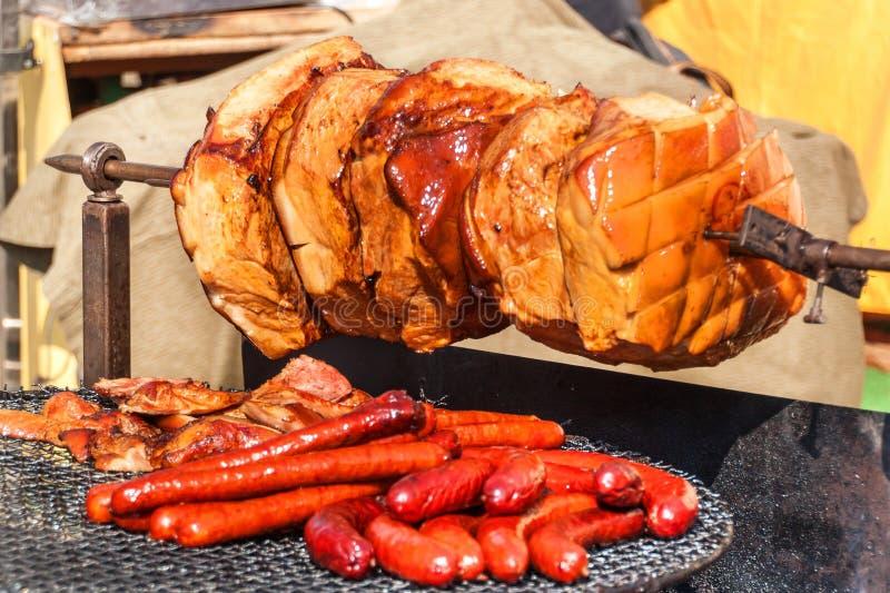 Schweinefleischschinkenfleisch wird auf dem offenen Feuer gebraten Tschechisches Lebensmittel der Straße im Grill Ungesundes fett stockfotos