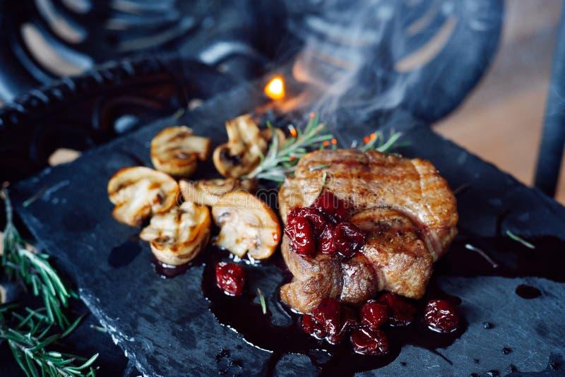 Schweinefleischsteak mit Pilzen und Kirsche sauce über Weinlesehintergrund auf Rauche lizenzfreie stockbilder