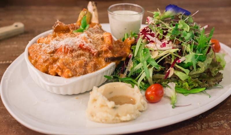 Schweinekotelett-französischer Schnitt mit Soße, organischem Salat und Kartoffelpüree mit Soße stockbild