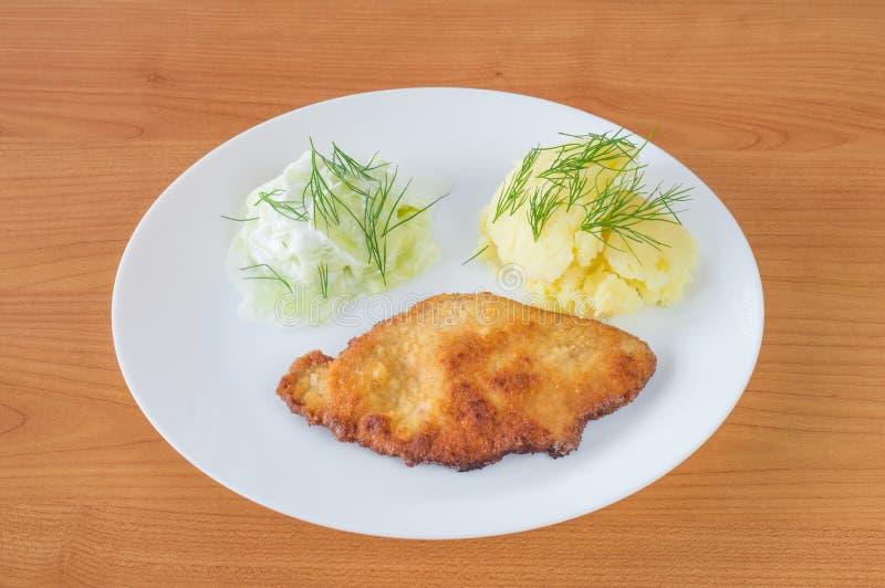 Schweinekotelett mit geschnittenen Gurken mit Sauerrahm und Kartoffelpürees lizenzfreie stockfotografie