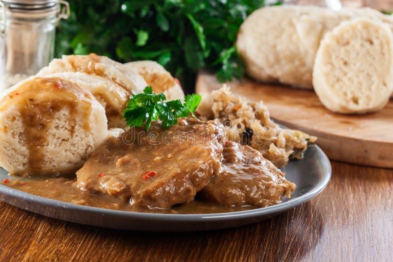 Schweinelende in der Soße mit Brotmehlklößen und -sauerkraut stockfotos