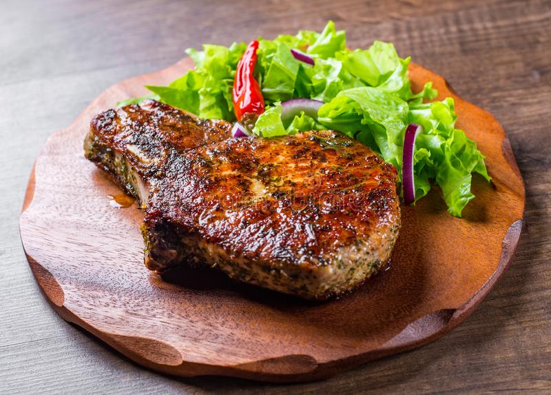 Schweinelende hackt mariniertes Fleisch Steak mit Gemüse slad auf Holztisch stockfotos
