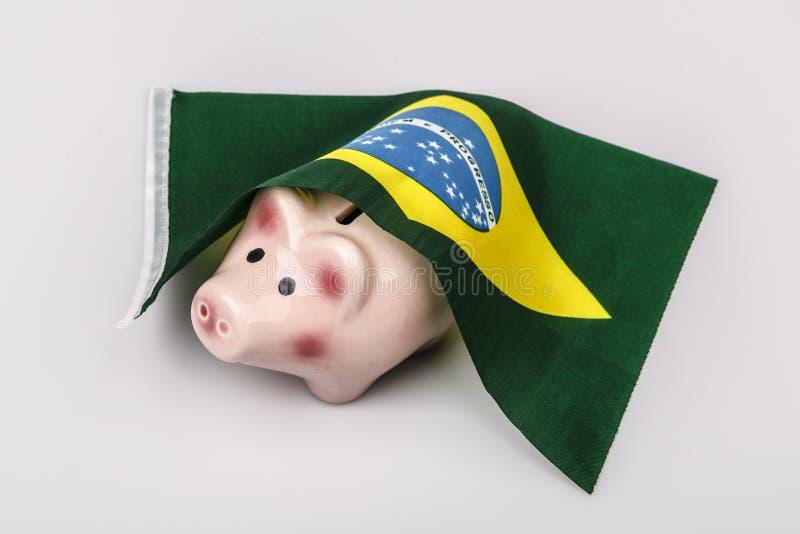 Schweingeldkasten und Brasilien-Flagge stockfotos