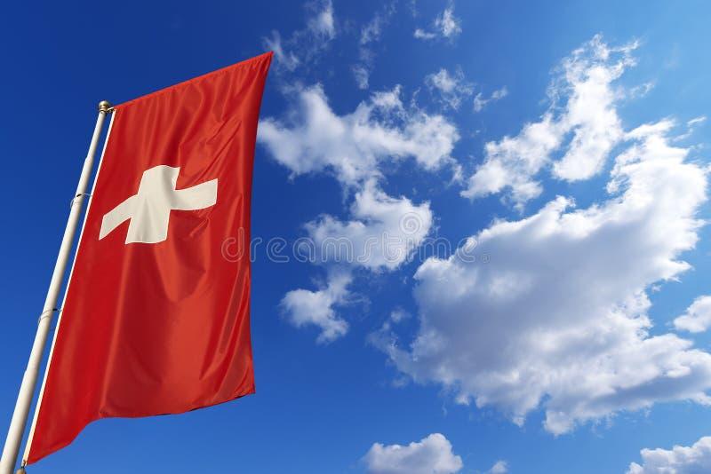 Schweiz flagga i blå himmel arkivfoton
