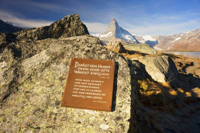 Schweiz Zermatt, Oktober 19, 2018: Minnes- minnestavla för psalmbibel för turister det klara vattnet av bergsjön Stellisee arkivfoto