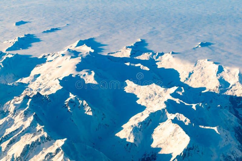 Schweizaren, Italien och österrikiska fjällängar med det snöig berget överträffar flyg- sikt in mot öst under eftermiddagflyg fotografering för bildbyråer