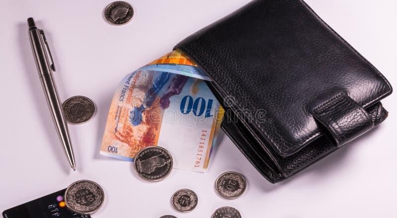Schweizer Banknoten und Münzen in einer Geldbörse auf einem Weiß stockbild