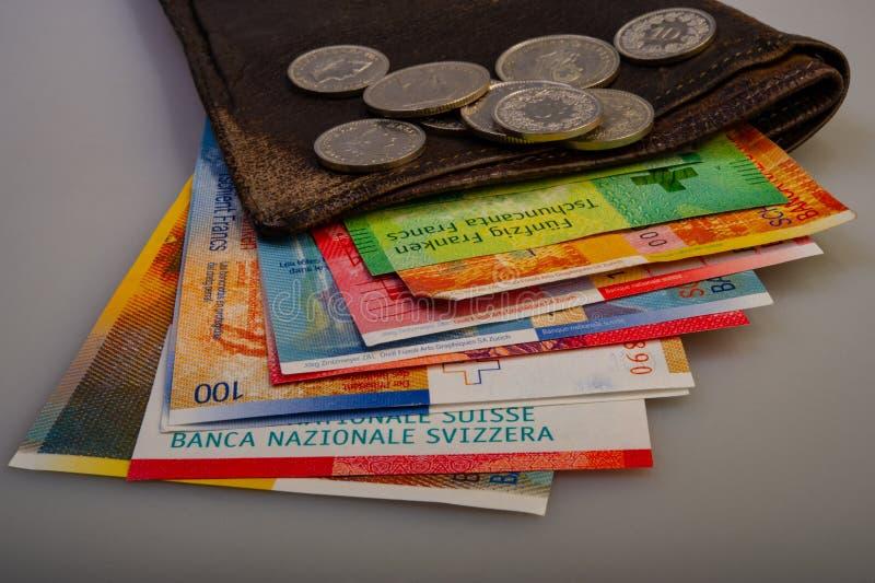 Schweizer Bargeldbanknoten, -münzen und -geldbeutel stockfotos
