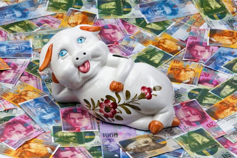Schweizer Franc und piggy Querneigung stockfotos