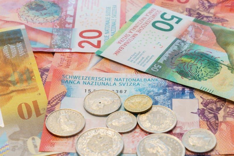 Schweizer Franken Banknoten und Münzen mit neuen zwanzig und fünfzig Rechnungen des Schweizer Franken stockbilder