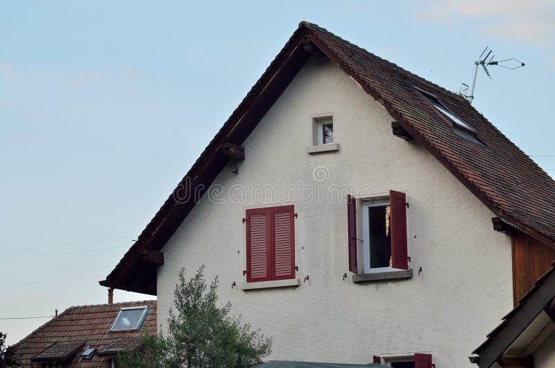 Schweizer Haus mit roten Fenstern lizenzfreie stockbilder