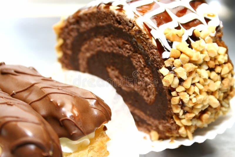 Schweizer Rolle mit Muttern und Schokolade und zwei Eclairs stockbild