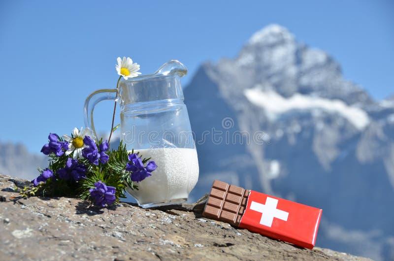 Schweizisk choklad och tillbringaren av mjölkar arkivfoton