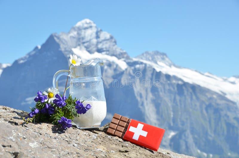 Schweizisk choklad och tillbringaren av mjölkar royaltyfri bild