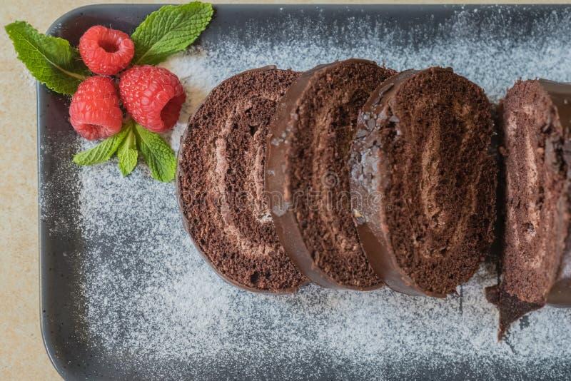 Schweizisk rulle för choklad med driftstopp som dekoreras med hallon på en platta Selektivt fokusera royaltyfria foton