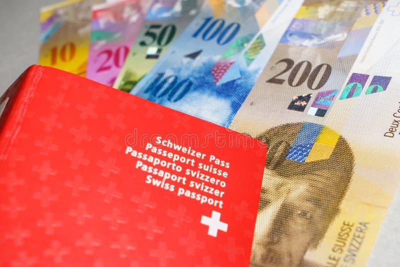 Schweiziskt pass och pengar royaltyfri fotografi