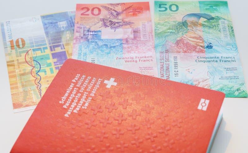 Schweiziskt pass och schweizisk franc med nya 20 och 50 schweizisk franc räkningar arkivfoto