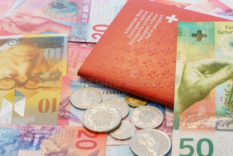 Schweiziskt pass och schweizisk franc med nya 20 och 50 schweizisk franc räkningar arkivbild