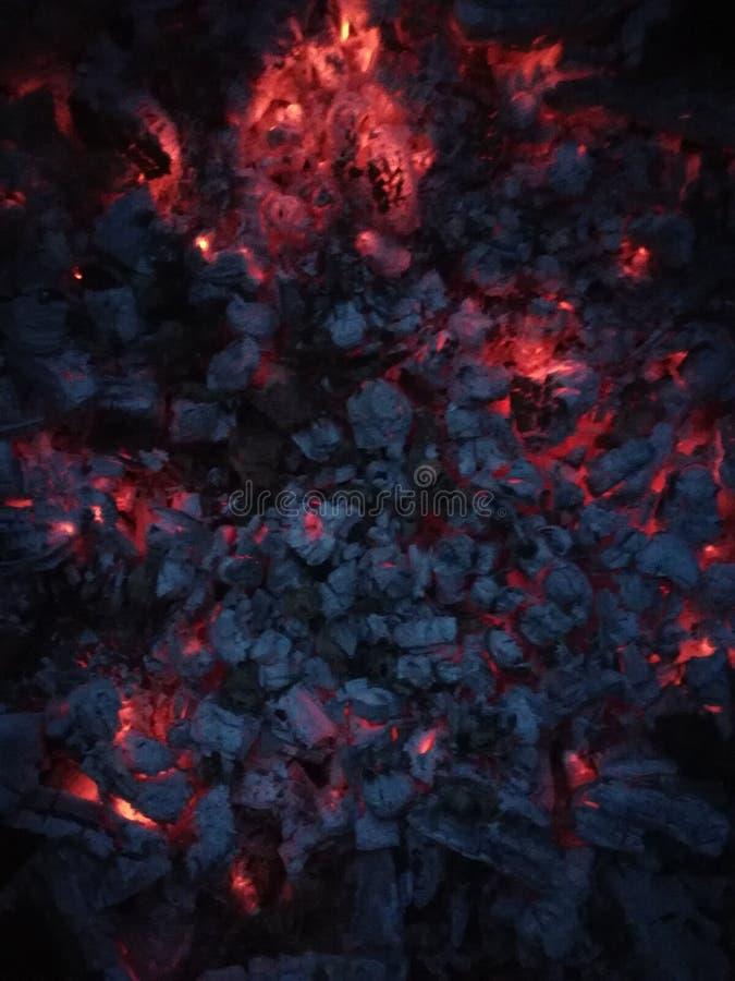 Schwelende rote Kohlen auf einem schwarzen Hintergrund lizenzfreies stockbild