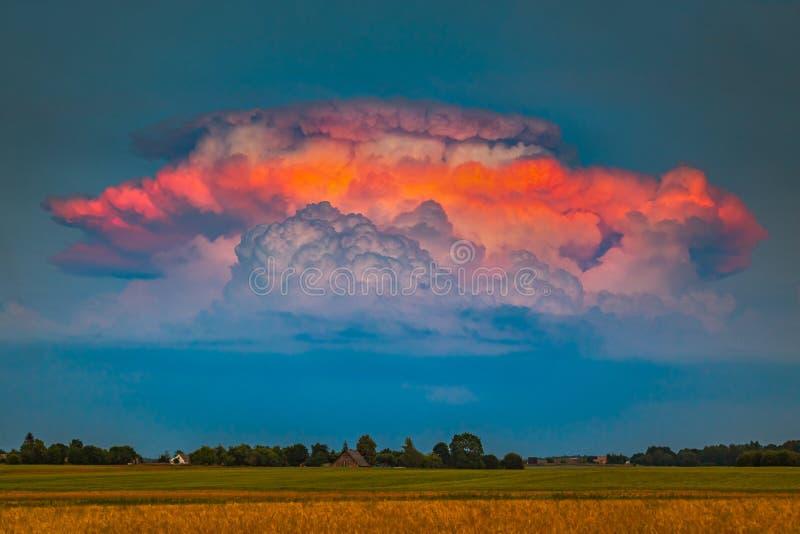 Schwere Impulsgewitter Cumulonimbuswolken iluminated durch die Glättung des roten Lichtes, ein seltener Moment stockfotografie