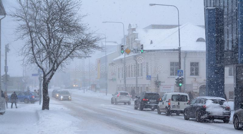 Schwere Schneefälle in der Stadt Die Autos, die Schnitt, einige Fußgänger und Schnee kreuzen, bedeckten Baum lizenzfreies stockfoto