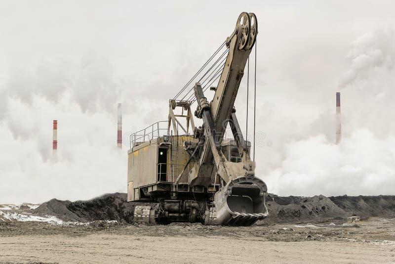 Schwerer Eimerbergbaubagger auf einer Gleiskette gegen einen Hintergrund des starken Smogs der dichten Fabrik mit rauchenden Schl lizenzfreie stockfotografie