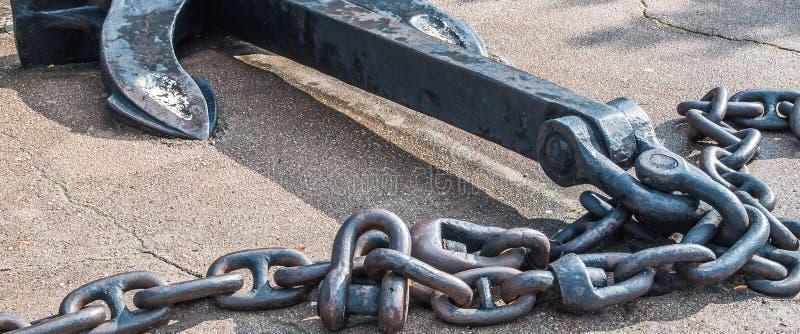 Schwerer Eisenmetallschiffsanker mit Kette auf grauem Asphalt lizenzfreie stockfotografie
