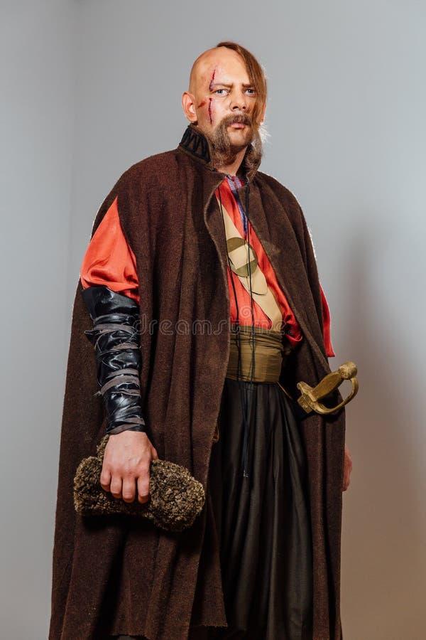 Schwerer Krieger russischer Kosake, Gesicht in den Narben, kahl Ausgeblutetes Blut Säbel in der Hülle stockfotografie