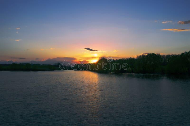 Schwerer Sonnenuntergang auf dem Fluss stockfoto