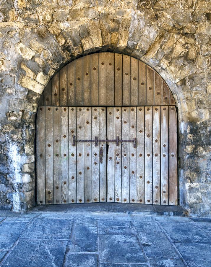 Schweres hölzernes Tor in einem alten Palast mit verrosteten Fensterläden und einem Schlüsselloch in der Steinwand stockbilder