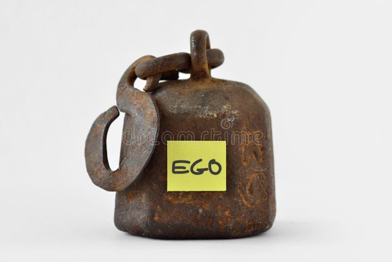 Schwergewicht mit dem Wort Ego geschrieben auf Papieranmerkung über weißes Ba stockfotos