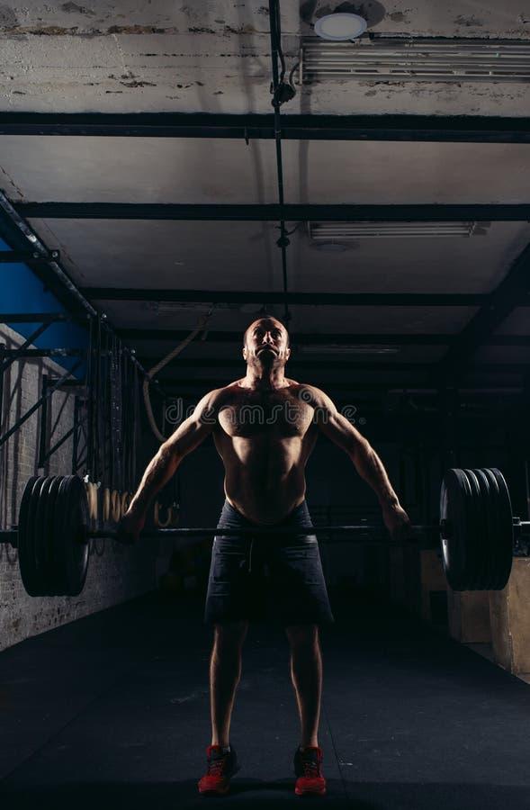 Schwergewichts- anhebende Stange der Crossfit-Eignungs-Turnhalle durch Training des starken Mannes stockfoto