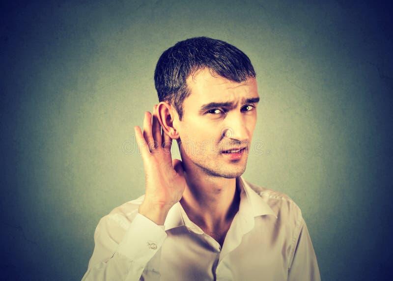 Schwerhöriger Mann, der Hand auf das Ohr bittet, oben zu sprechen setzt stockfoto