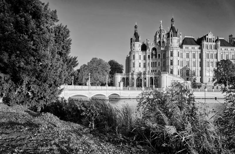 Schwerin castle in black and white with trees by the lake. Germany. Black-and-white, autumn, bridge, palace, europe, architecture, building, landmark, tourism stock photos