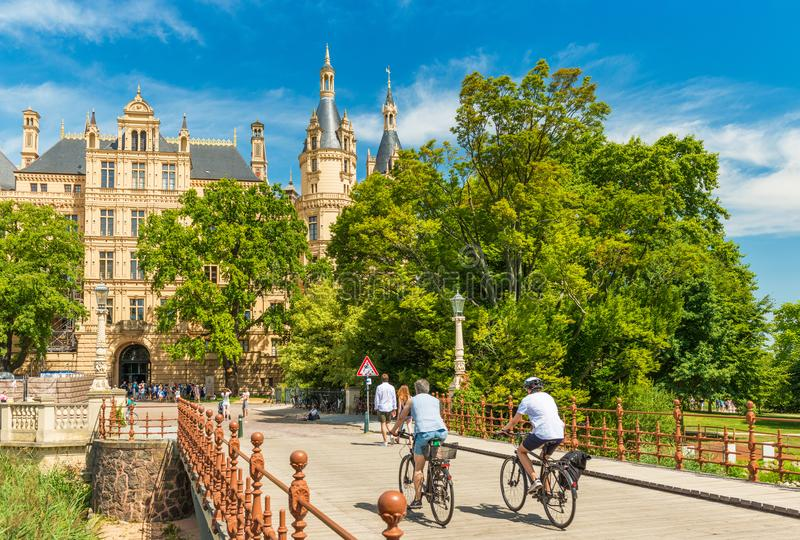 Schwerin, Germany: Two cyclists moving towards the Schwerin Castle stock photo