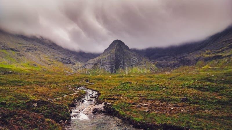 Schwermütige Landschaftsansicht von Cuillin-Hügeln mit Fluss im Vordergrund, Schottland stockfotos