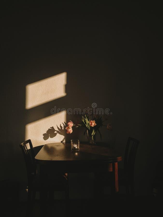 Schwermütige schöne Blumen auf einem hölzernen Weinleseschreibtisch und dem Morgen sonnen das Glänzen stockbilder
