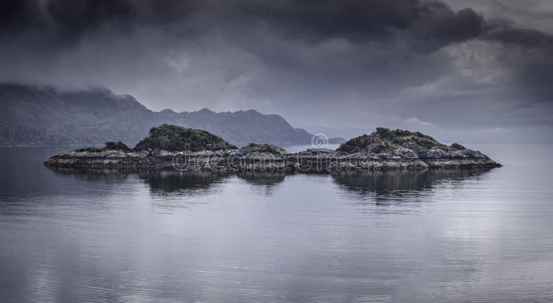 Schwermütiger Himmel über See mit Inseln Sch?ne Landschaft von Schottland, Gro?britannien stockbild