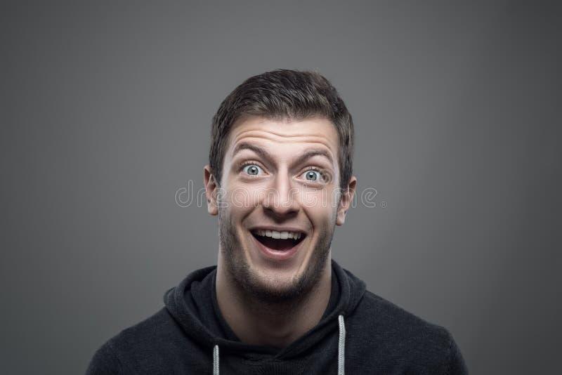 Schwermütiges Porträt des überraschten ausdrucksvollen jungen Mannes, der Kamera betrachtet lizenzfreie stockbilder