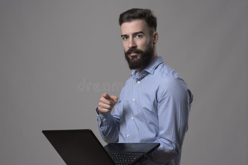 Schwermütiges Porträt des überzeugten ernsten erfolgreichen jungen Mannes auf Laptop Finger auf die Kamera zeigend, die Sie wählt stockfotografie