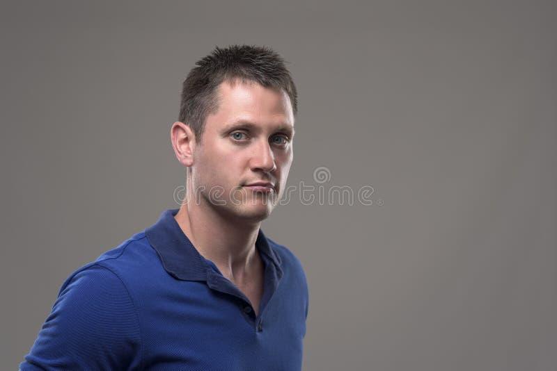 Schwermütiges Porträt des ernsten überzeugten jungen Mannes im blauen Polohemd, das Kamera betrachtet stockfotografie
