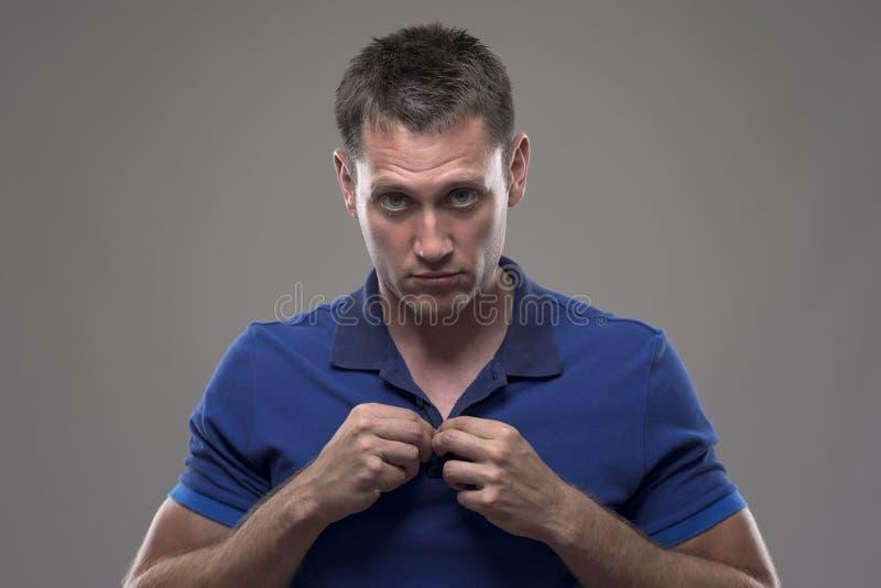 Schwermütiges Porträt des jungen gestörten Mannes, der Polohemdkragen knöpft und Kamera betrachtet lizenzfreie stockbilder