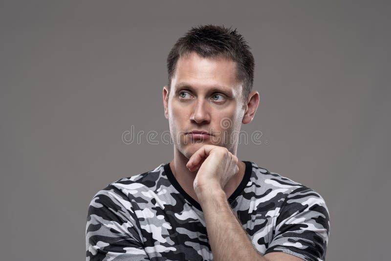 Schwermütiges Porträt des nachdenklichen durchdachten Mannes, der weg schaut, denkend mit der Hand auf Kinn stockfoto