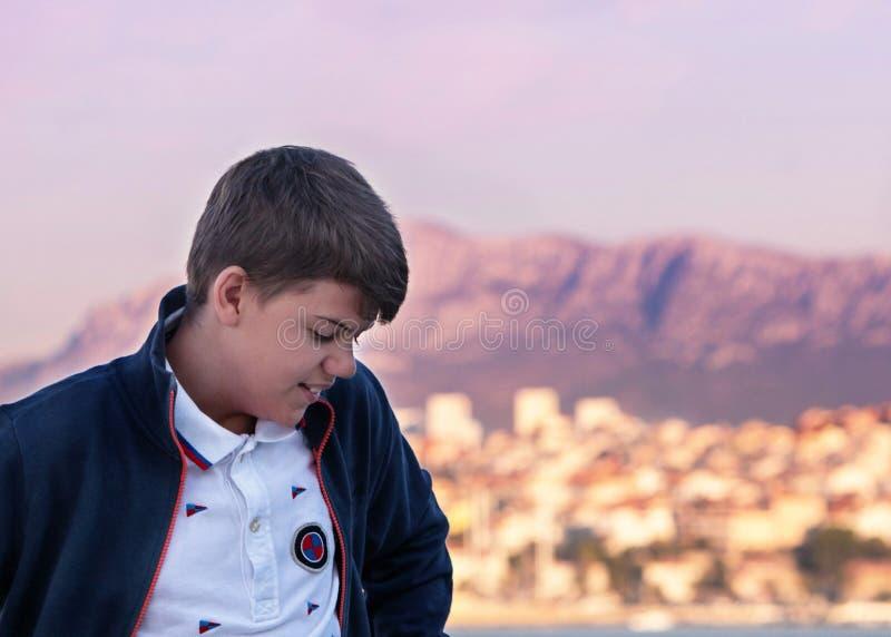 Schwermütiges Porträt mit kroatischen Dorfskylinen am Hintergrund Allein smyling Junge lizenzfreies stockbild