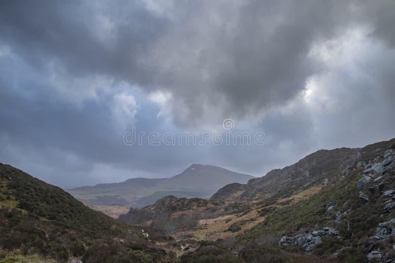Schwermütiges und drastisches Winterlandschaftsbild von Moel Saibod von Crimpiau in Snowdonia mit erstaunlichen Lichtstrahlen in  lizenzfreie stockfotografie
