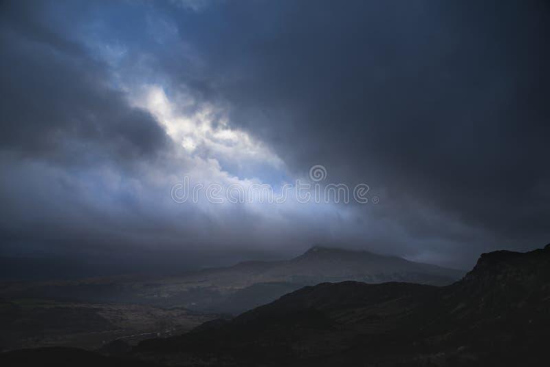 Schwermütiges und drastisches Winterlandschaftsbild von Moel Saibod von Crimpiau in Snowdonia mit erstaunlichen Lichtstrahlen in  lizenzfreies stockfoto