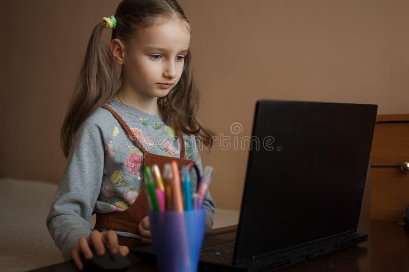 Schwerwiegende kleine Mädchen konzentriert sich vor ihrem schwarzen Laptop, während sie sich während der Quarantäne auf Hausaufga stockbilder