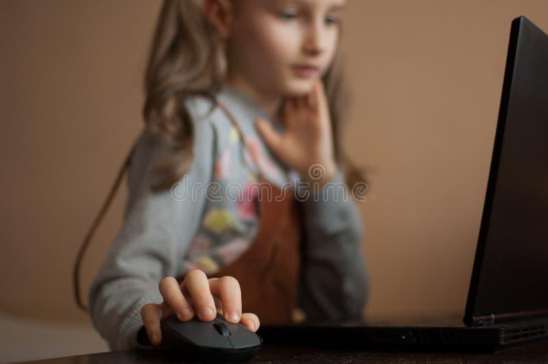 Schwerwiegende kleine Mädchen konzentriert sich vor ihrem schwarzen Laptop, während sie sich während der Quarantäne auf Hausaufga stockbild